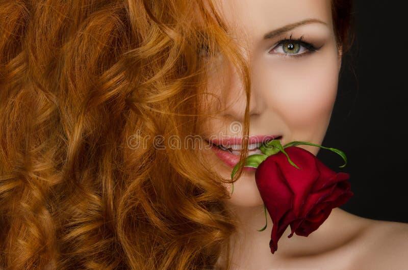 La mujer con los controles rojos del pelo subió en su boca fotografía de archivo libre de regalías