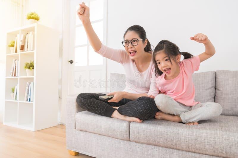 La mujer con los niños que ven la TV se divierte el canal fotos de archivo
