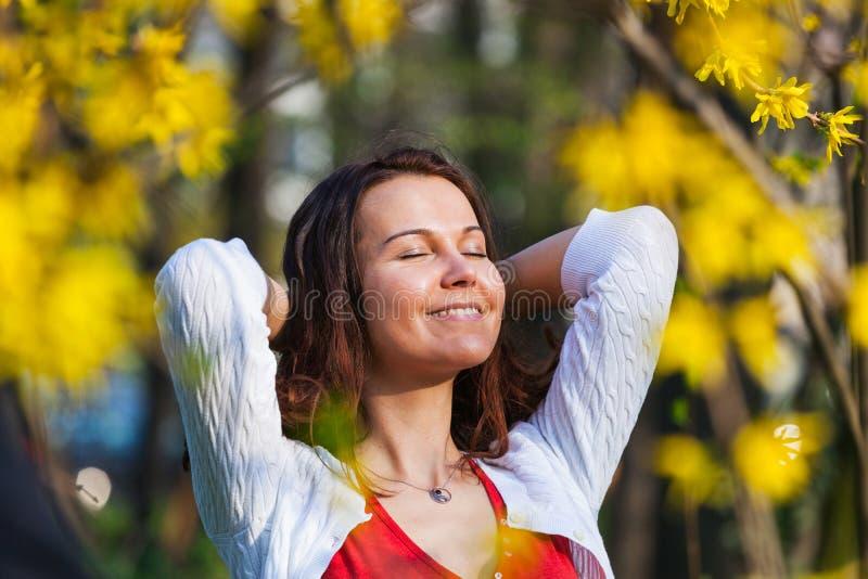 La mujer con los ojos cerrados está gozando del sol imagen de archivo