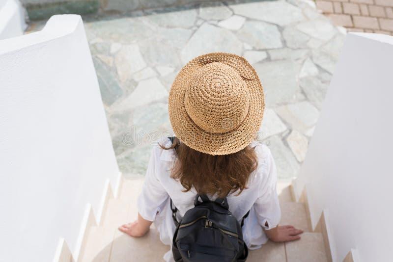 La mujer con la mochila en un sombrero de paja se sienta en los pasos y se relaja de la ciudad de vacaciones Viajero individual foto de archivo
