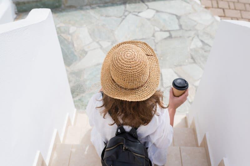 La mujer con la mochila en un sombrero de paja y la taza de café de papel se sienta en los pasos y se relaja de la ciudad de vaca imágenes de archivo libres de regalías