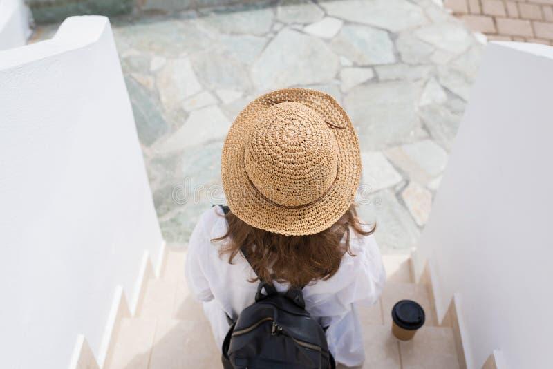 La mujer con la mochila en un sombrero de paja y la taza de café de papel se sienta en los pasos y se relaja de la ciudad de vaca imagen de archivo