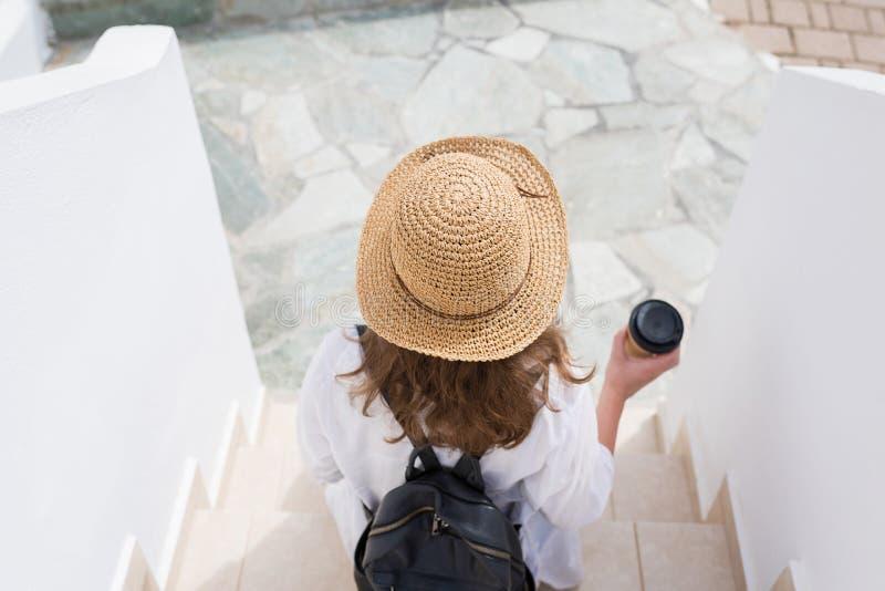 La mujer con la mochila en un sombrero de paja y la taza de café de papel se sienta en los pasos y se relaja de la ciudad de vaca fotos de archivo libres de regalías