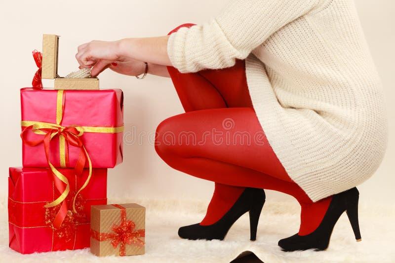 La mujer con muchas cajas de regalo que abren la caja de oro con la joya gotea imagenes de archivo