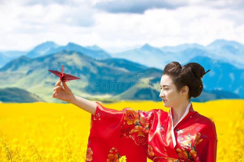 La mujer con papiroflexia crane en el campo floreciente amarillo fotos de archivo libres de regalías