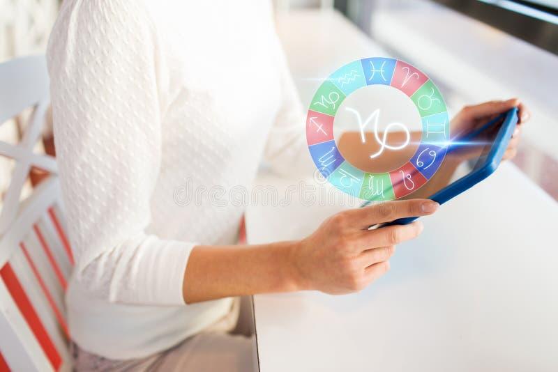 La mujer con PC y el zodiaco de la tableta firma en el café foto de archivo