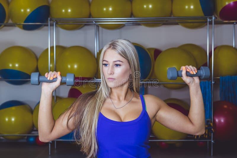 La mujer con pesas de gimnasia cupo el cuerpo delgado del ABS aislado en un backg blanco imágenes de archivo libres de regalías