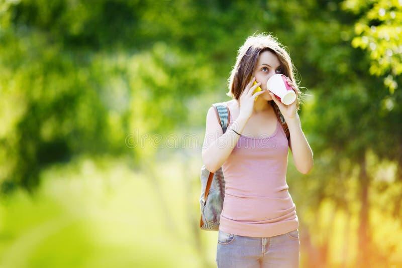 La mujer con smartphone y el café en día de verano parquean fotografía de archivo