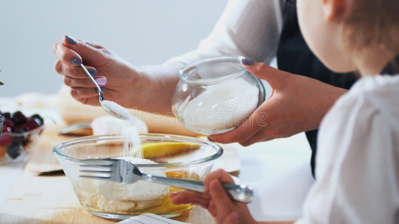 La mujer con su niño pone el azúcar en la pasta para preparar las crepes imagen de archivo