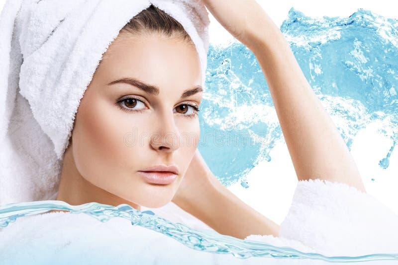 La mujer con la toalla de baño en la cabeza en agua salpica fotos de archivo