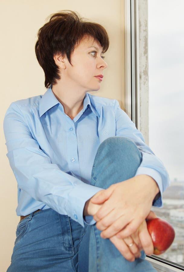 La mujer con una manzana se sienta cerca de una ventana imagen de archivo libre de regalías