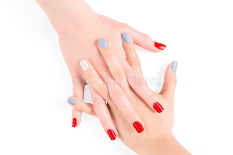 La mujer conectó las manos con el esmalte de uñas rojo y azul de la laca foto de archivo