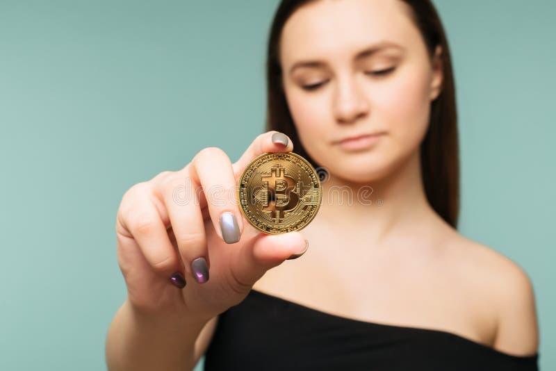 La mujer confiada acertada joven lleva a cabo un bitcoin del oro en su mano fotografía de archivo