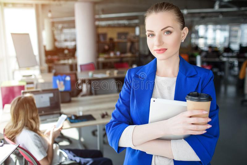 La mujer confiada y profesional se está colocando en la oficina y está sosteniendo una taza de café También ella tiene un cuadern imágenes de archivo libres de regalías