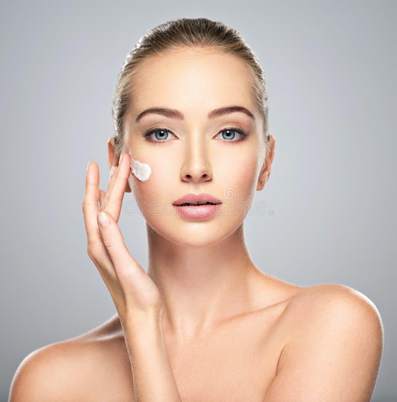 La mujer consigue la crema en la cara Concepto del cuidado de piel fotografía de archivo libre de regalías