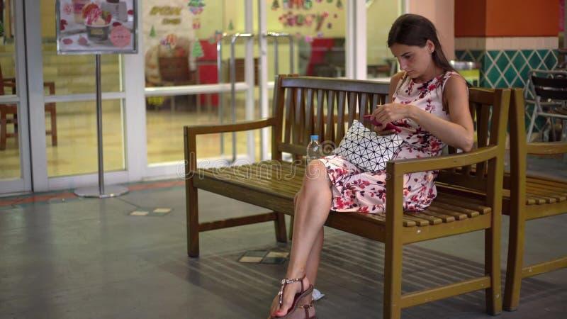 La mujer consigue el mensaje y toma el teléfono para leerlo que sonríe imágenes de archivo libres de regalías