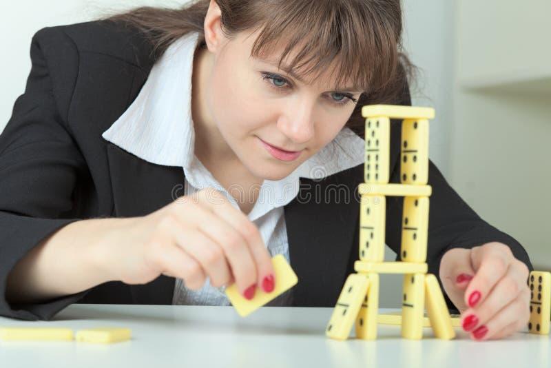 La mujer construye la torre de los huesos de los dominós en el vector fotografía de archivo