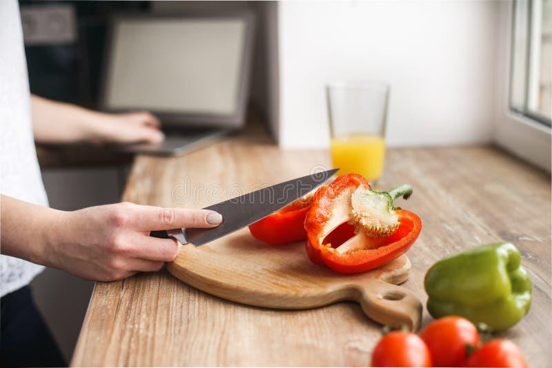 La mujer cortó las pimientas Ella mira cómo preparar un plato Vea la receta en Internet fotografía de archivo libre de regalías