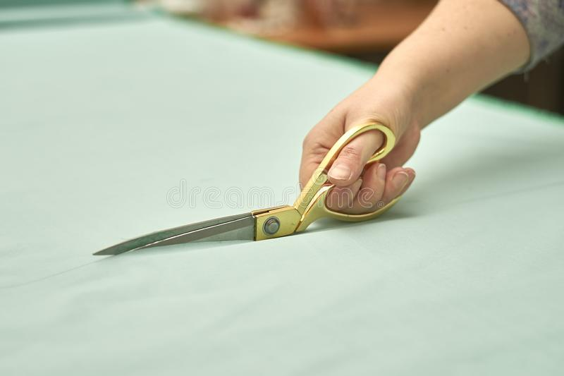 La mujer corta el material verde con las tijeras de oro fotos de archivo libres de regalías