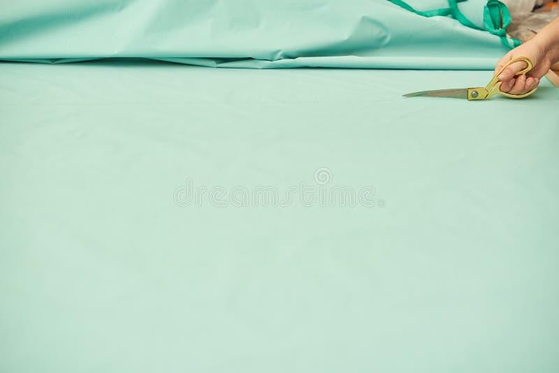 La mujer corta el material verde con las tijeras de oro imagenes de archivo