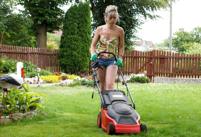 La mujer corta la hierba foto de archivo