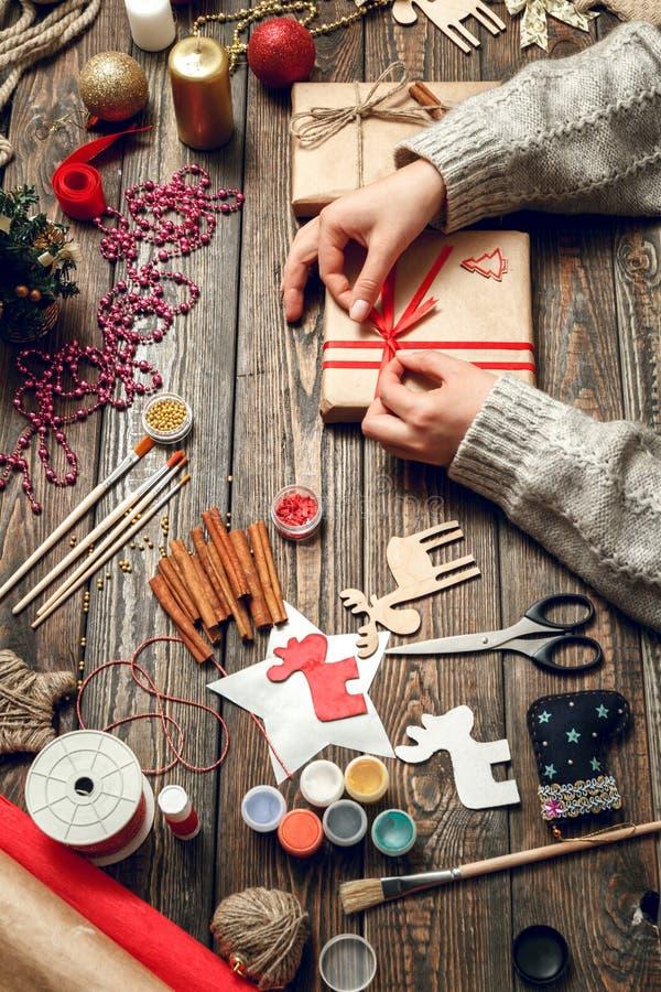 La mujer crea los regalos elegantes de la Navidad foto de archivo