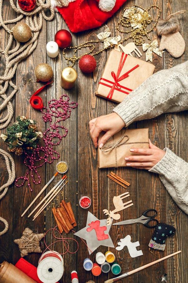 La mujer crea los regalos elegantes de la Navidad imagen de archivo