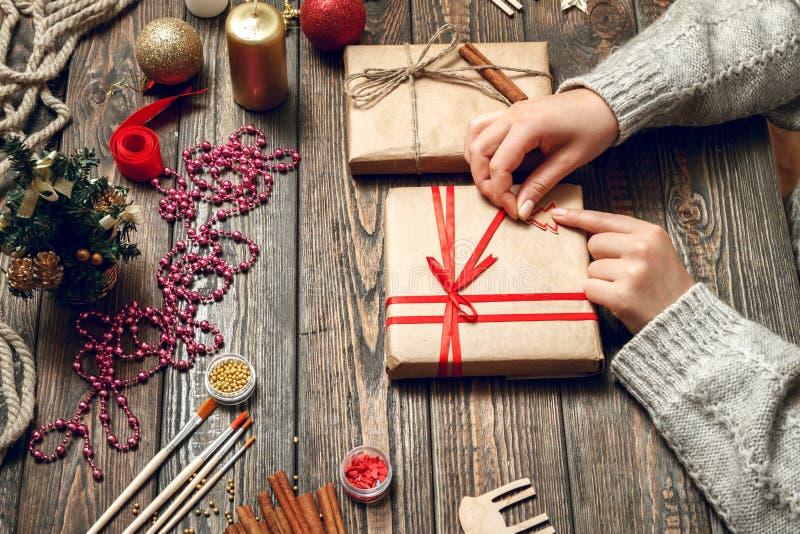 La mujer crea los regalos elegantes de la Navidad fotografía de archivo