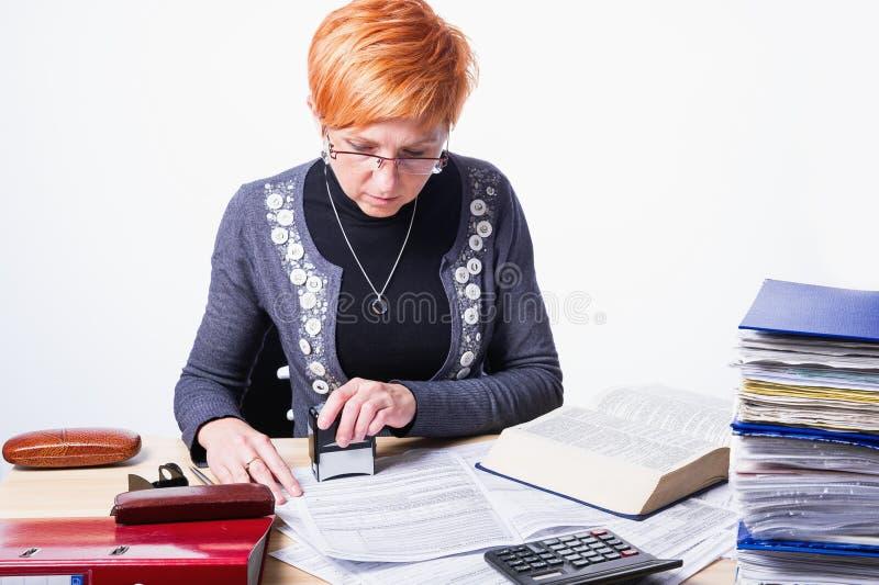 La mujer cuenta impuestos foto de archivo