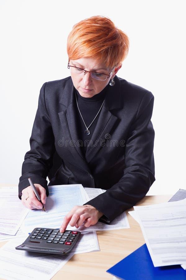 La mujer cuenta impuestos fotografía de archivo libre de regalías