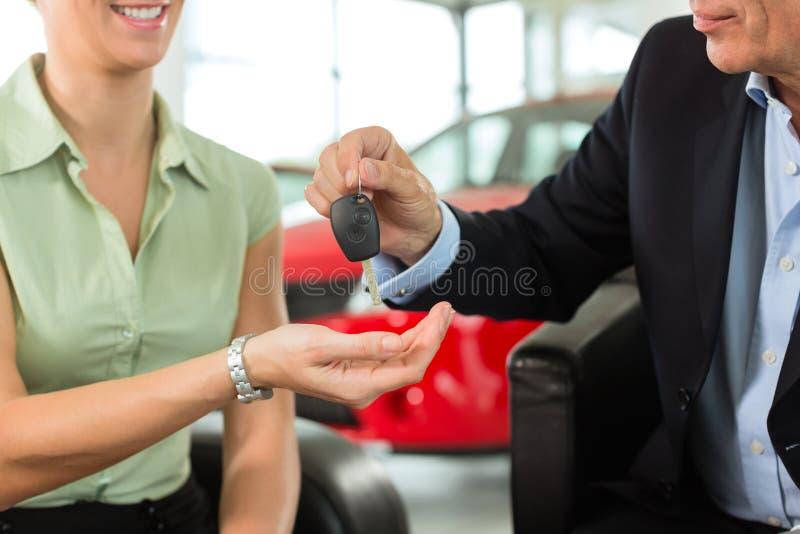 La mujer da claves del coche al hombre en el distribuidor autorizado auto foto de archivo