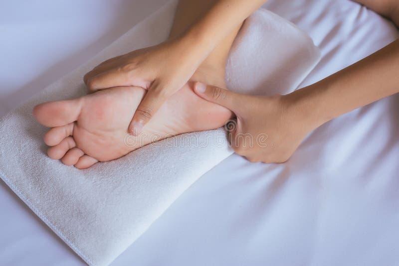 La mujer da el donante de masaje a su pie en el dormitorio, massag de los lenguados del pie fotos de archivo