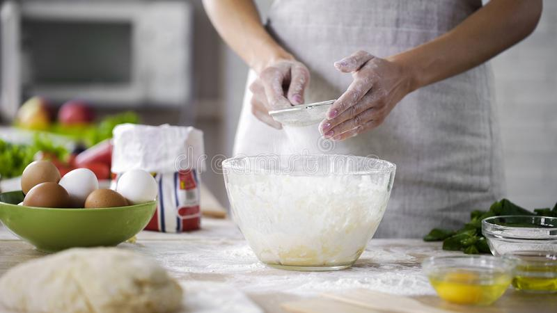 La mujer da el tamizado de la harina sobre el bol de vidrio con la pasta, añadiendo los ingredientes de la hornada fotografía de archivo libre de regalías