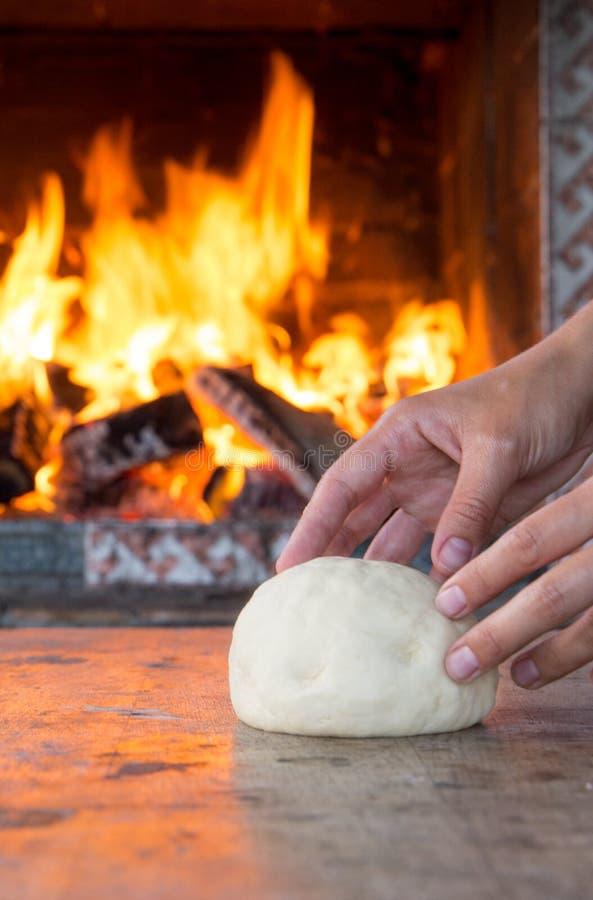 La mujer da la fabricación de la pasta cruda fresca para la hornada de la pizza o del pan en la tabla de madera contra la chimene fotos de archivo libres de regalías