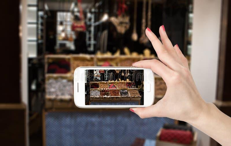 La mujer da la foto en línea con un teléfono elegante imagen de archivo