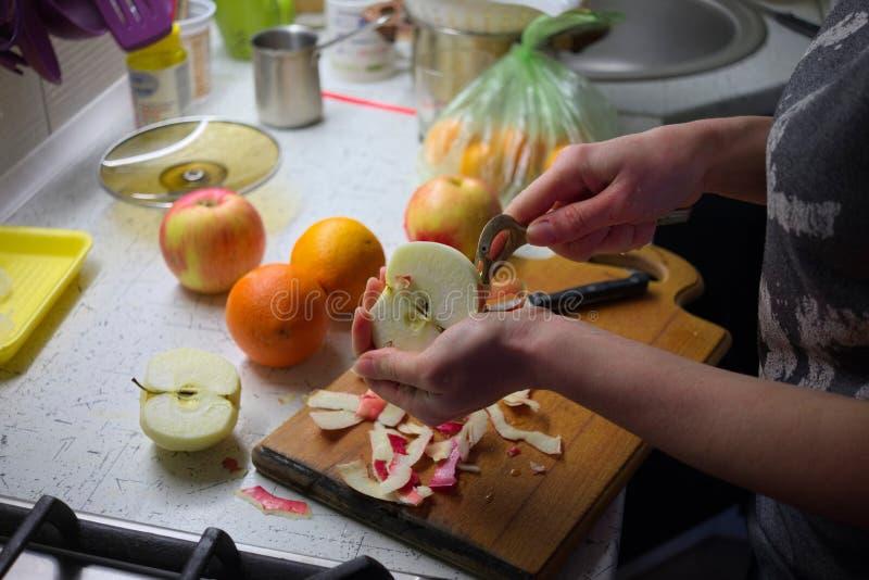 La mujer da la manzana de la peladura con el cuchillo en la cocina que prepara las frutas frescas imagen de archivo libre de regalías
