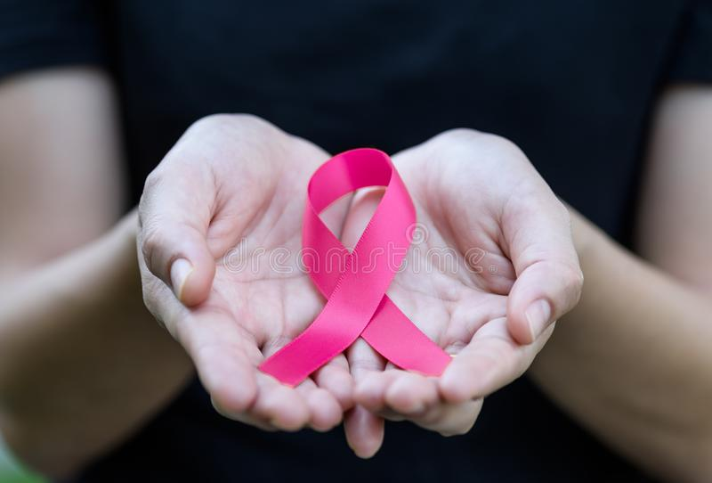 La mujer da sostener la cinta rosada para el cáncer de pecho favorable foto de archivo