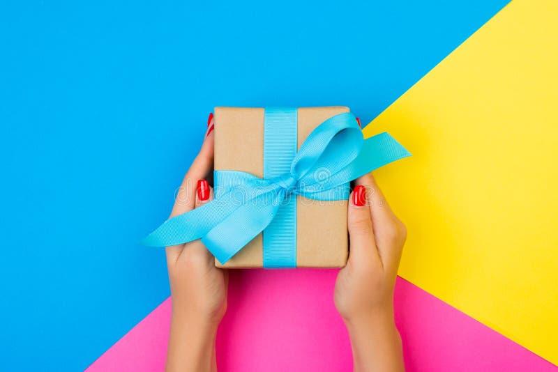La mujer da sostener el regalo envuelto y adornado con el arco azul en fondo azul, rosado y amarillo con el espacio de la copia imagen de archivo
