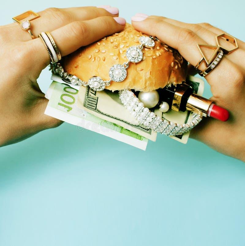 La mujer da sostener la hamburguesa con el dinero, joyer?a, cosm?tico, cierre social del concepto de la riqueza del problema para fotos de archivo libres de regalías