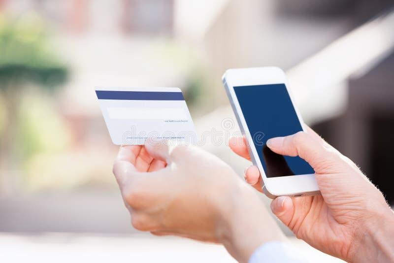 La mujer da sostener la tarjeta de crédito y usar la célula, teléfono elegante fotos de archivo libres de regalías