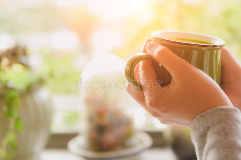 La mujer da sostener la taza caliente de café o de té por mañana imagenes de archivo