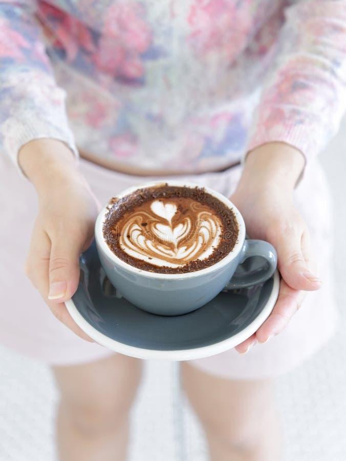 La mujer da sostener la taza de bebida caliente con arte del latte, en forma de corazón imágenes de archivo libres de regalías