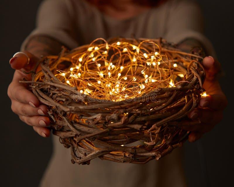 La mujer da sostener una jerarquía con las luces en fondo oscuro fotos de archivo libres de regalías