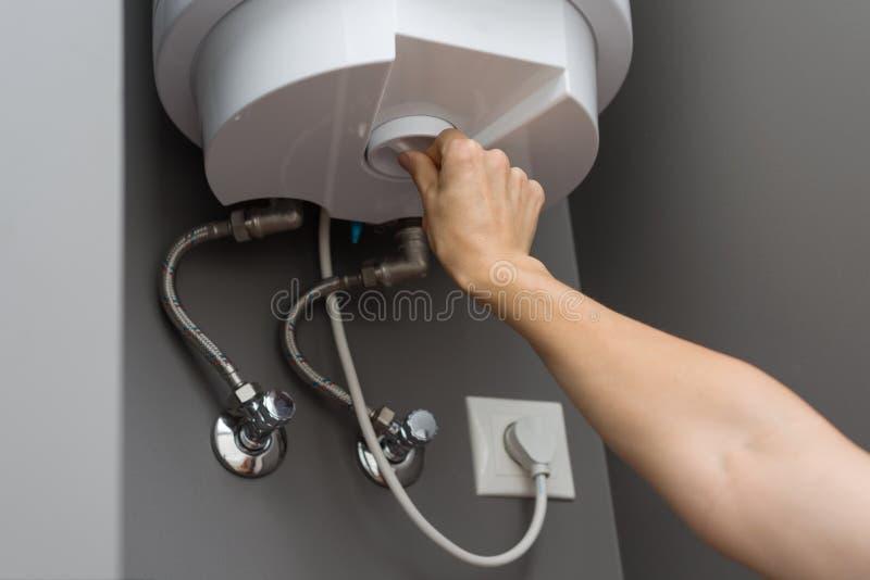 La mujer da la temperatura del ajuste del agua en caldera eléctrica del calentador El interior detalla el primer foto de archivo libre de regalías