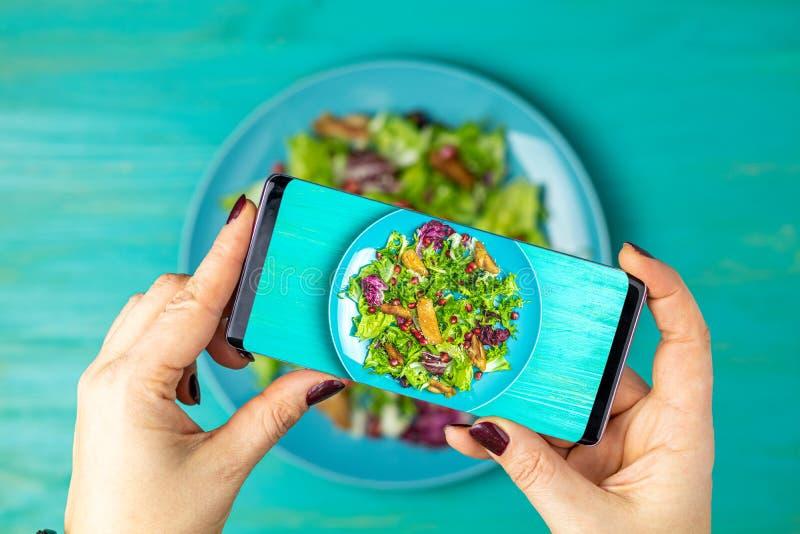 La mujer da tomar la foto de la comida por el tel?fono m?vil fotos de archivo libres de regalías