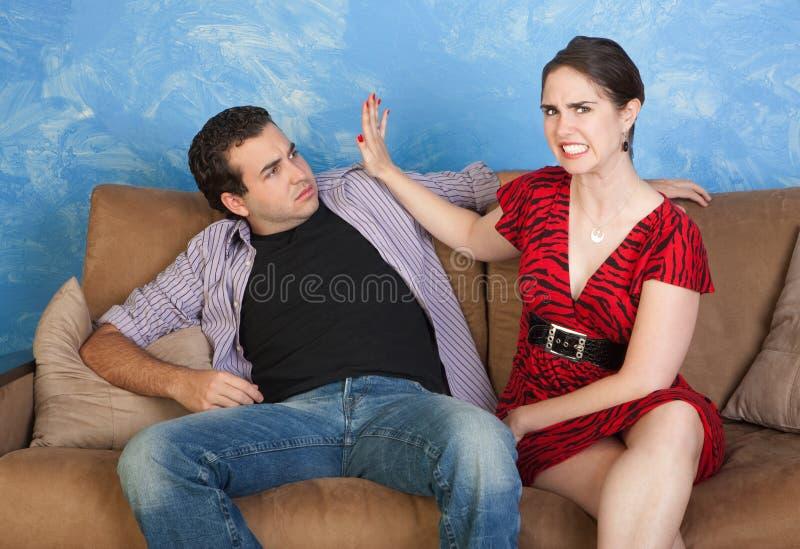 La mujer da una palmada al hombre imagenes de archivo