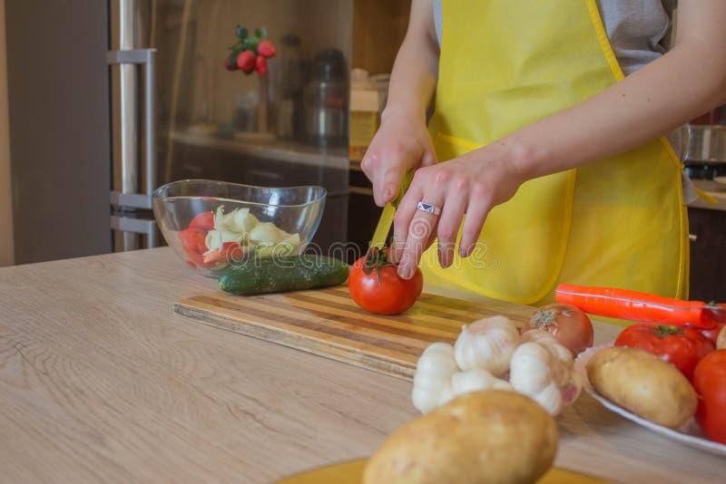 La mujer da verduras del corte en la pizarra de la cocina Alimento sano Mujer que prepara veh?culos fotos de archivo libres de regalías