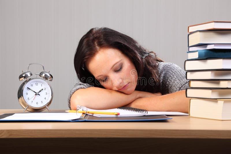 La mujer de última hora de la preparación se cae dormido en el escritorio imagen de archivo