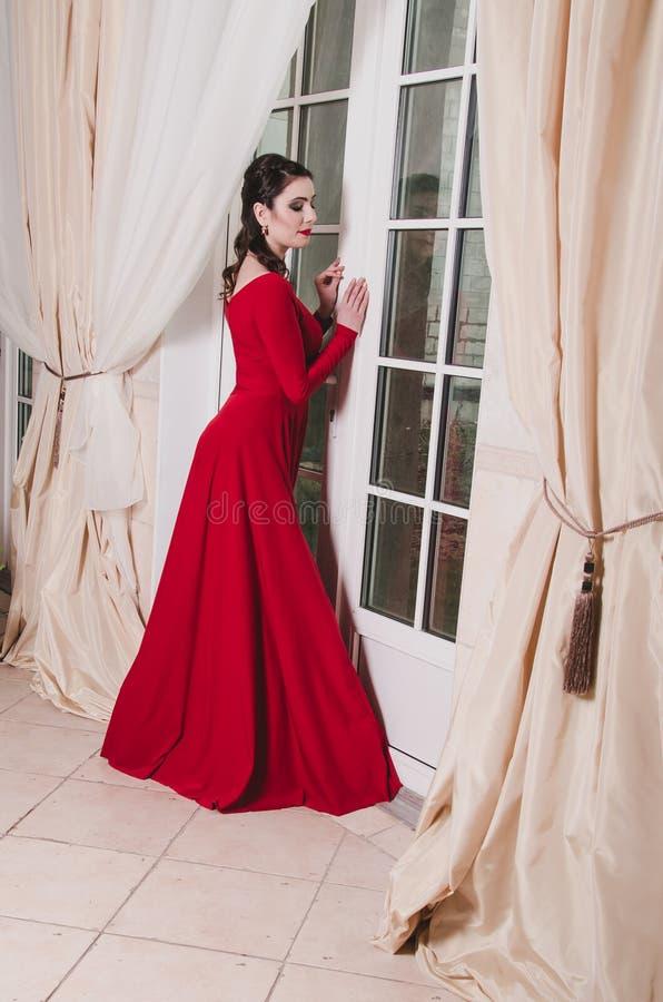 La mujer de 30 años morena elegante adulta en vestido rojo largo hace una pausa la puerta grande de la ventana Interior beige clá fotos de archivo