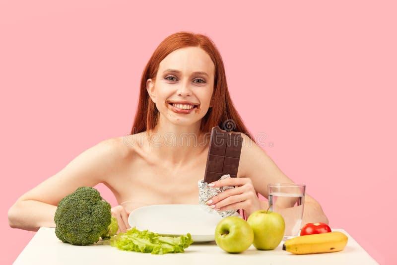 La mujer de Anorexi siente feliz mientras que come el chocolate en vez de verduras sanas imagen de archivo libre de regalías